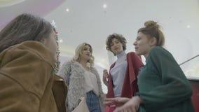 Grupo de colegas de trabalho fêmeas que saem na alameda comprar presentes do Natal para sua família - filme