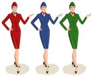 Grupo de 3 comissárias de bordo vestidas no uniforme com variações da cor Fotografia de Stock Royalty Free