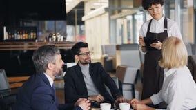 Grupo de compañeros de trabajo que hablan con la camarera en el café que hace orden durante hora de la almuerzo almacen de video