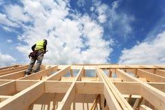 Grupo de construção que trabalha no telhado contra o céu azul Fotos de Stock