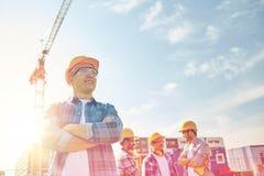 Grupo de constructores sonrientes en cascos de protección al aire libre imagen de archivo libre de regalías