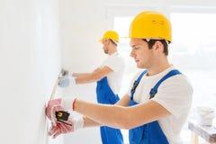 Grupo de construtores com fita de medição dentro Fotos de Stock