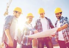 Grupo de construtores com PC e modelo da tabuleta fotografia de stock