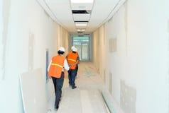 Grupo de construtores e de arquitetos que supervisionam o progresso do trabalho imagem de stock
