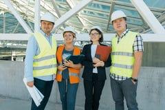 Grupo de coordenadores, construtores, arquitetos no terreno de construção Conceito da construção, do desenvolvimento, dos trabalh imagem de stock royalty free