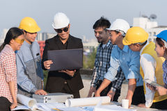 Grupo de coordenadores e de arquitetos em um canteiro de obras imagem de stock