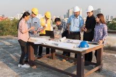 Grupo de coordenadores e de arquitetos que aplanam em um canteiro de obras foto de stock