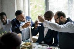 Grupo de copas de vino que tintinean de la gente diversa junto foto de archivo libre de regalías
