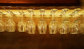 Grupo de copas de vino vacías que cuelgan en el estante de la barra en fondo del filtro del vintage Fotografía de archivo