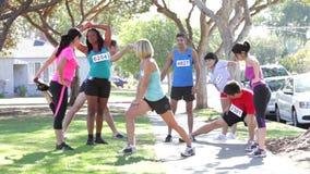 Grupo de corredores que aquecem-se antes da raça filme