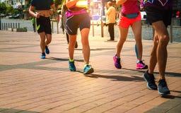 Grupo de corredores que correm ao longo da estrada no por do sol fotos de stock