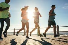 Grupo de corredores que corren en el camino por la playa Foto de archivo libre de regalías