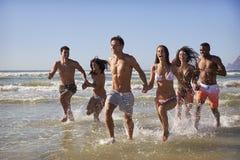 Grupo de corrida dos amigos através das ondas junto em férias da praia foto de stock