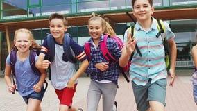 Grupo de corrida feliz dos estudantes da escola primária filme