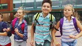 Grupo de corrida feliz dos estudantes da escola primária