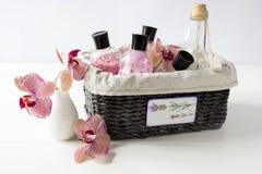 Grupo de cosméticos para o cuidado do corpo em uma cesta de vime em uma tabela branca foto de stock royalty free