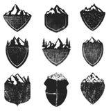 Grupo de crachás do Grunge com as montanhas isoladas no fundo branco ilustração do vetor