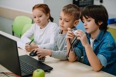 grupo de crianças adoráveis que trabalham junto para construir o robô, haste fotos de stock