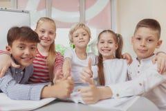 Grupo de crianças bonitos que tiram junto na classe de arte fotografia de stock