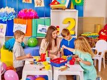 Grupo de crianças com o professor fêmea que pinta junto Foto de Stock Royalty Free