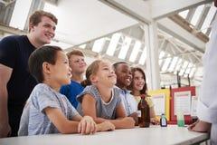 Grupo de crianças com os professores que têm o divertimento em um centro da ciência imagem de stock royalty free