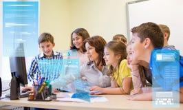 Grupo de crianças com professor e computador na escola imagens de stock