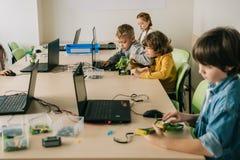 grupo de crianças concentradas que trabalham em projetos na haste fotos de stock royalty free