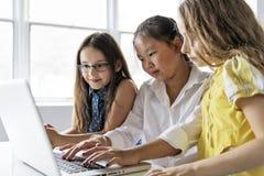Grupo de crianças curiosas que olham o material na tela do portátil imagens de stock