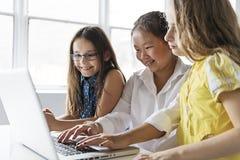 Grupo de crianças curiosas que olham o material na tela do portátil foto de stock royalty free