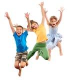 Grupo de crianças desportivos alegres do barefeet feliz que saltam e que dançam imagens de stock