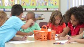 Grupo de crianças elementares da idade que usam penas da coloração filme