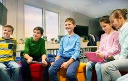 Grupo de crianças felizes com o PC da tabuleta na escola fotografia de stock royalty free