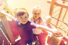 Grupo de crianças felizes no campo de jogos das crianças Imagens de Stock