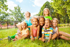 Grupo de crianças felizes no gramado no parque Fotografia de Stock Royalty Free