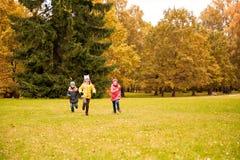 Grupo de crianças felizes que correm fora Fotos de Stock