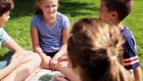 Grupo de crianças felizes que sentam-se na grama e na fala video estoque
