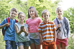 Grupo de crianças Geocaching nas madeiras imagem de stock