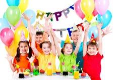Grupo de crianças na festa de anos com mãos levantadas Fotos de Stock