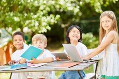 Grupo de crian?as no curso de computador de uma escola prim?ria fotos de stock