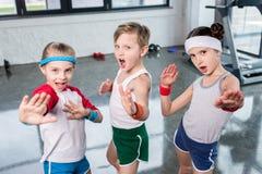 Grupo de crianças no sportswear que exercitam e que levantam na câmera no gym fotografia de stock royalty free