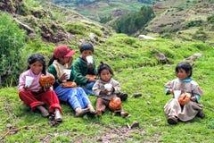 Grupo de crianças peruanas que compartilham do café da manhã do Natal que senta-se na grama que come o pão fotografia de stock royalty free