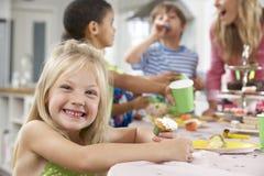 Grupo de crianças que apreciam o alimento da festa de anos na tabela Fotografia de Stock Royalty Free
