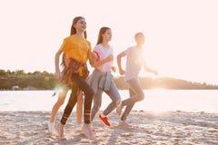 Grupo de crianças que correm na praia Acampamento de verão fotografia de stock