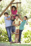 Grupo de crianças que escalam a escada de corda à casa na árvore Imagens de Stock