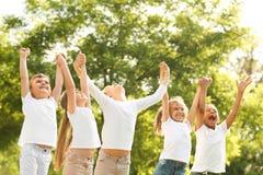 Grupo de crianças que guardam as mãos acima no parque imagem de stock