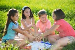 Grupo de crianças que jogam na grama Fotos de Stock