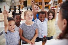 Grupo de crianças que oferecem-se para responder à pergunta do professor fotos de stock royalty free