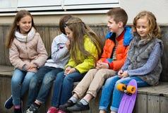 Grupo de crianças que sentam-se no banco Foto de Stock Royalty Free