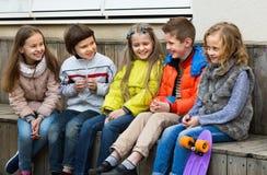 Grupo de crianças que sentam-se no banco Fotos de Stock Royalty Free