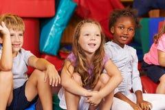 Grupo de crianças que sentam-se no gym da escola fotos de stock